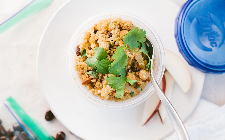 <![CDATA[Bol de quinoa épicé et de pois chiches garni de raisins secs et d'amandes grillées]]>