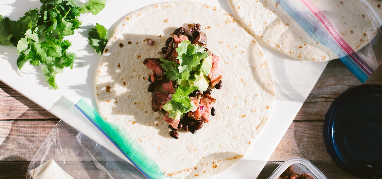 <![CDATA[Burritos au bœuf et haricots noirs garnis d'oignons rouges et d'avocat]]>