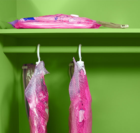Two Ziploc Space Bags hanging off a closet rack and one placed on the top shelf.
